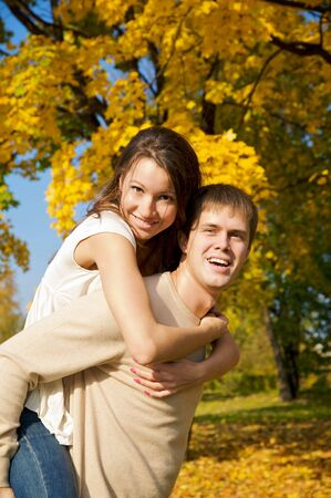 Happy young couple play piggyback in the autumn park Stock Photo - 3817583
