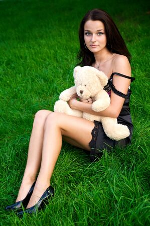 Young sexy woman sitting on a green grass with teddy bear photo