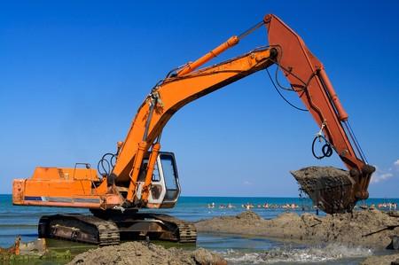 excavate: Orange Excavator on the beach Stock Photo