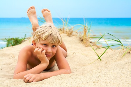 Young blond boy lying on the beach