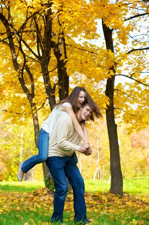 Happy young couple play piggyback in the autumn park Stock Photo