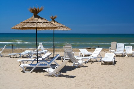 Parasols and empty chaise-longue on a beach Stock Photo - 4169072