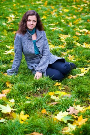 Beautiful young woman sitting in a autumn park photo