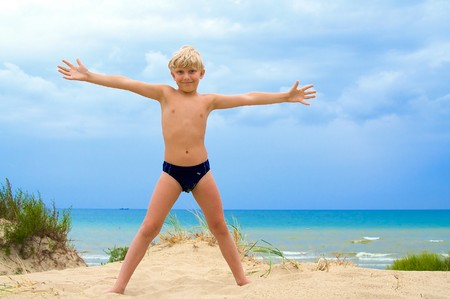 Happy young boy with his arms wide open in the sandy beach