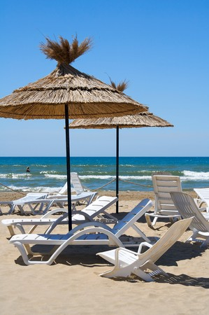 Parasols and empty chaise-longue on a beach Stock Photo - 4224344