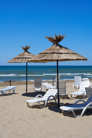 Parasols and empty chaise-longue on a beach Stock Photo - 4224343