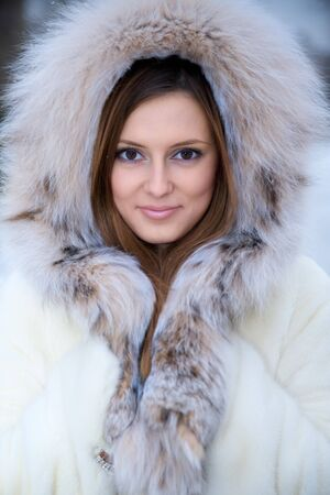 fur hood: Beautiful young woman in winter fur coat. Winter portrait