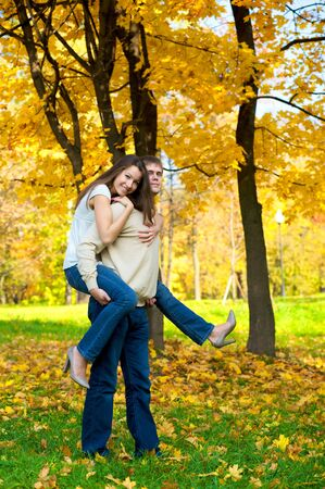 Happy young couple play piggyback in the autumn park Stock Photo - 4306708