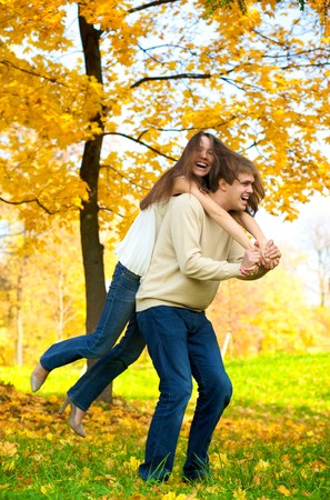 Happy young couple play piggyback in the autumn park Zdjęcie Seryjne
