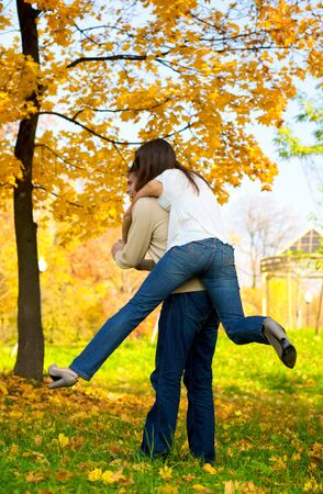Happy young couple play piggyback in the autumn park Stock Photo - 4306707