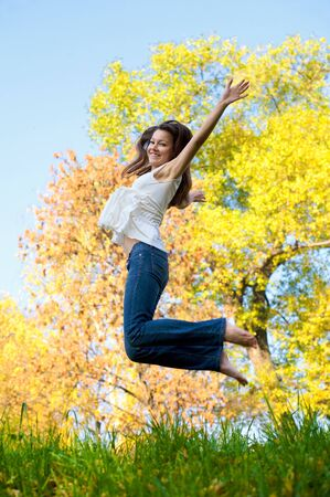 Happy beautiful girl jumping of joy on a fall day Stock Photo