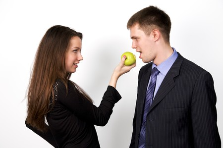 Young happy couple playfully eating apple photo