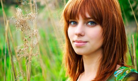 Portrait of a young beautiful woman with red hair in thick grass Stock Photo