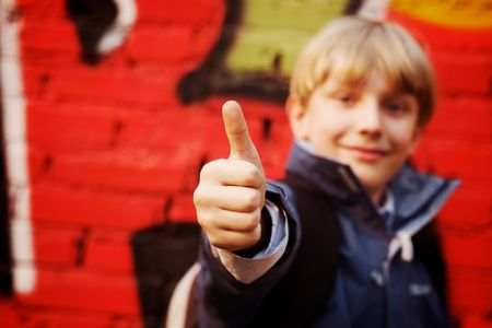dof: Cool kid standing in front of a graffiti wall. Focus in hand (selective DOF)