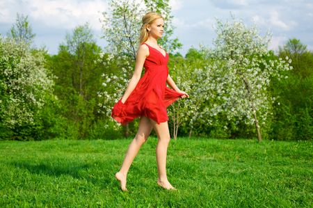 Young beautiful woman in a red dress running in green meadow