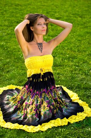 Young beautiful woman sitting on the green grass in sun-dress photo