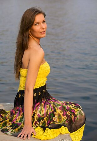 Portrait of a young beautiful woman near the river photo