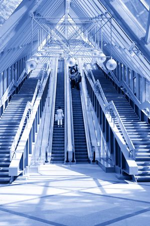 escalate: People standing on escalator in modern business center. Tint blue