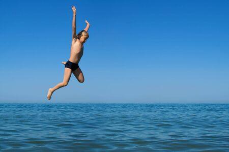 Yang boy jumping into the sea