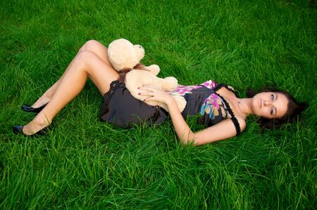 Young beautiful women lying on green grass with teddy bear photo
