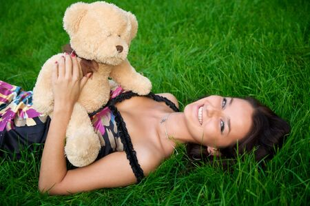 Young smiling women lying on green grass with teddy bear photo