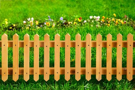 Wooden garden fence against green grass and flowers photo