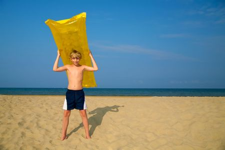 Young boy with air mattress on summer beach photo