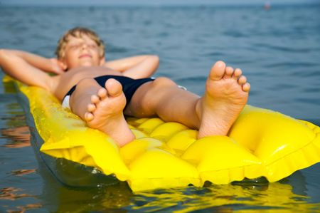 Young boy swimming on air mattress in the sea photo