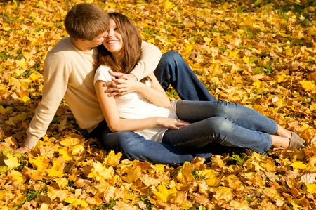 Happy young couple in love meeting on the autumn leaf photo