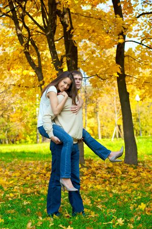 Happy young couple play piggyback in the autumn park photo