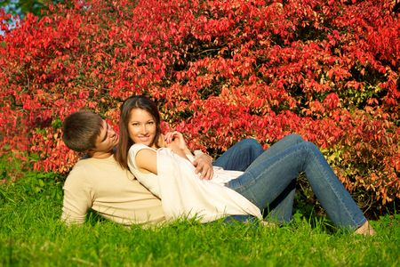 Happy young couple in love meeting in the autumn park with red leaves photo