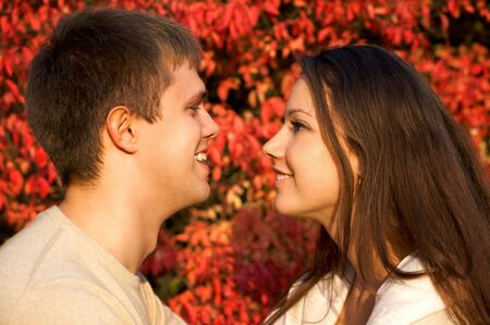 Happy young couple face to face in the autumn park with red leaves photo
