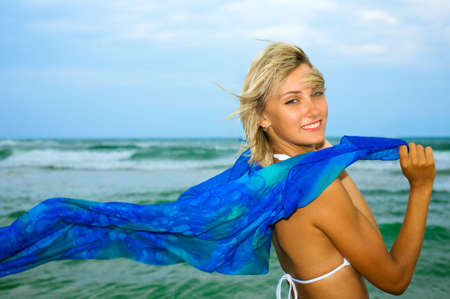 Beautiful happy woman enjoys freedom on tropical beach photo