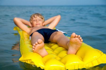 De natación Niño en el colchón de aire en el mar