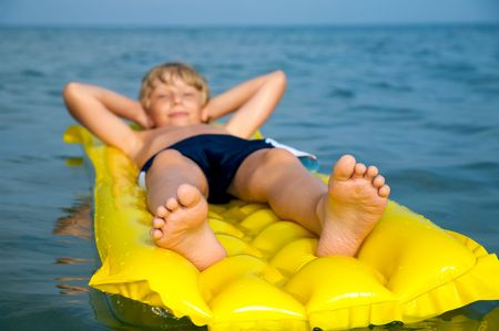 Young boy swimming on air mattress in the sea