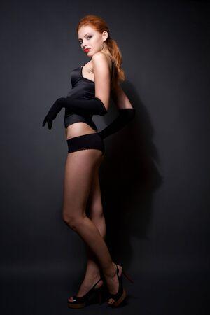 Attractive redhead model posing on studio dark background Stock Photo - 6368104