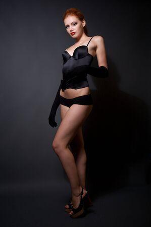 Attractive redhead model posing on studio dark background photo