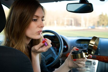 Young pretty woman preparing her make-up in car  photo