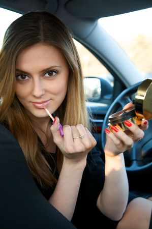 Young pretty woman preparing her make-up in car