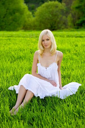 Beautiful young woman on field in a white dress Stock Photo - 6368180