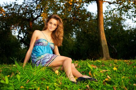 Young beautiful woman sitting in the autumn forest Stock Photo - 6368177