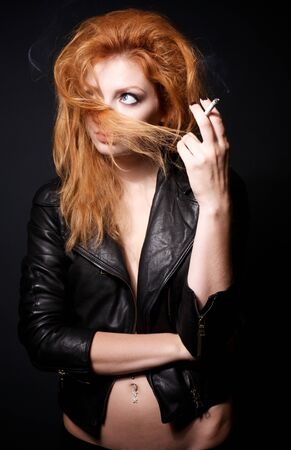 Portrait of beautiful young redhead woman with a cigarette photo