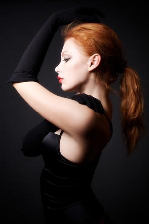 Attractive redhead model posing on studio dark background Stock Photo