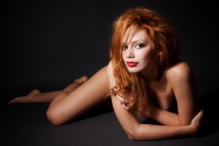 Young beautiful nude woman lies on the floor