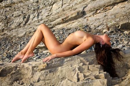 Beautiful naked woman on a stone beach Stock Photo