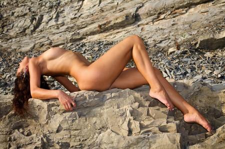 femme se deshabille: Belle femme nue sur une plage de Pierre Banque d'images