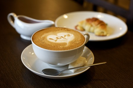 romantic picture: Coffee cup with milk and heart shape (selective DOF)