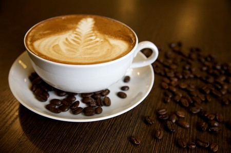Latte art on a cappucinno and coffee-beans (selective DOF) Stock Photo - 6937296