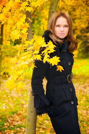 Young beautiful woman in a black coat in the autumn forest Stock Photo - 6928950