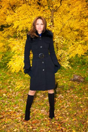 Young beautiful woman in a black coat in the autumn forest Stock Photo - 6928974